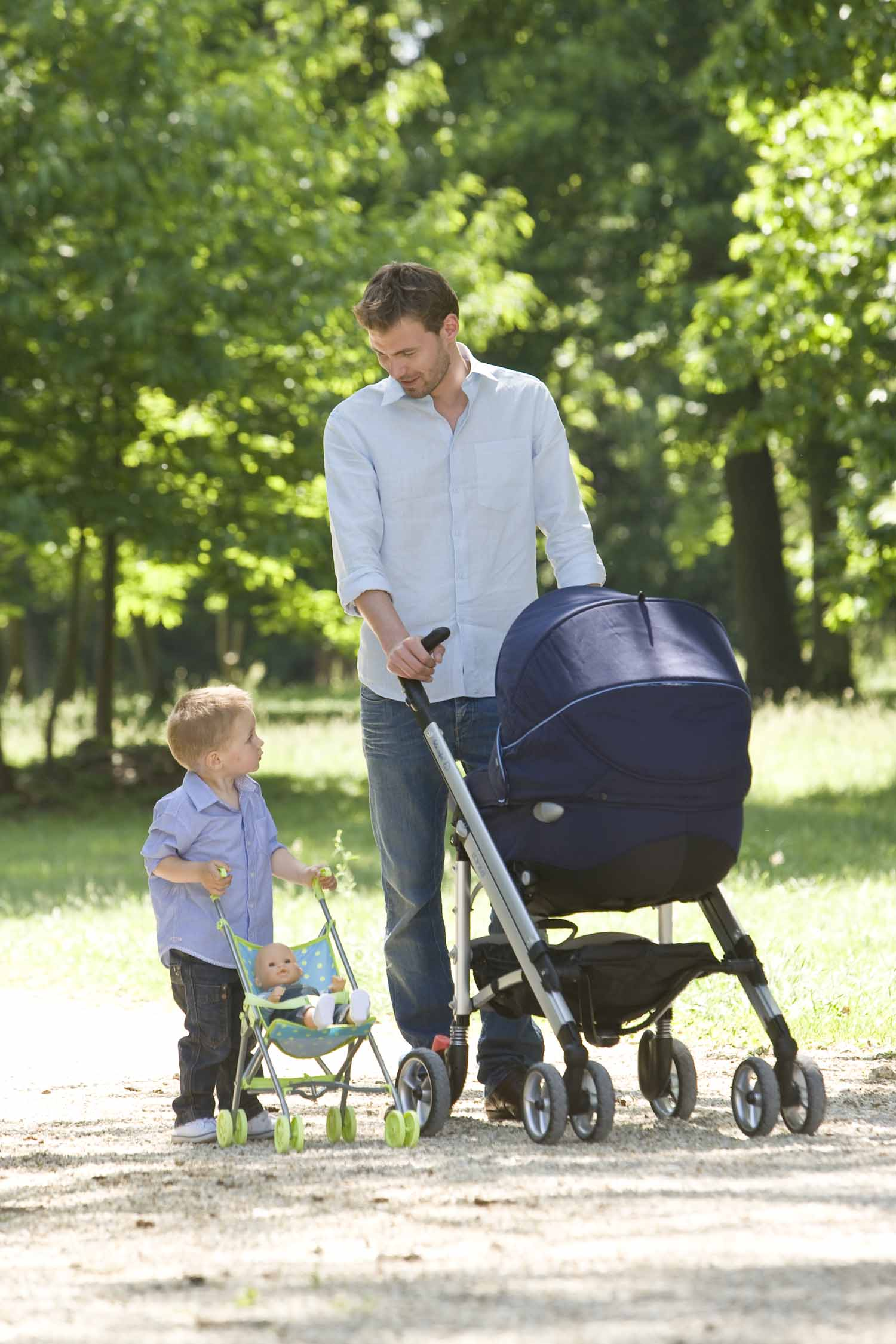 Father and boy playing with Corolle Doll and Stroller